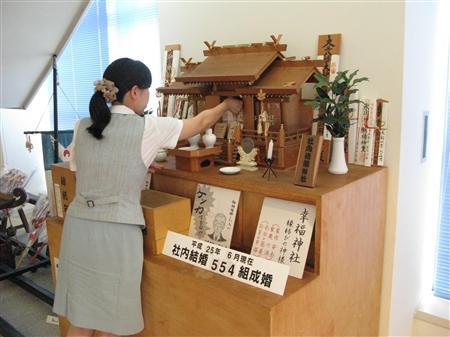 社内結婚神社に絵馬を奉納する日本食研ホールディングスの女性社員(同社提供)