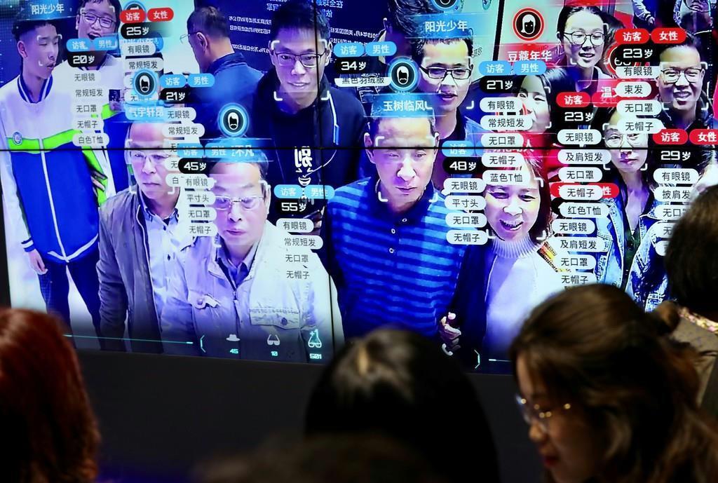 中国のデジタル技術博覧会で、顔認証技術を適用され、スクリーンに映しだされた訪問客ら=8日、福建省福州市(ロイター)