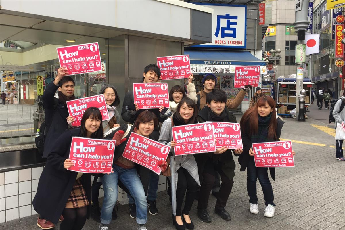 """Street volunteers with a sign """"How can I help you?"""" At a scrambled intersection in Shibuya (provided by Japan Local Buddy)"""